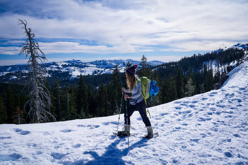 Woman snowshoeing at Castle Pass overlooking mountains in Tahoe