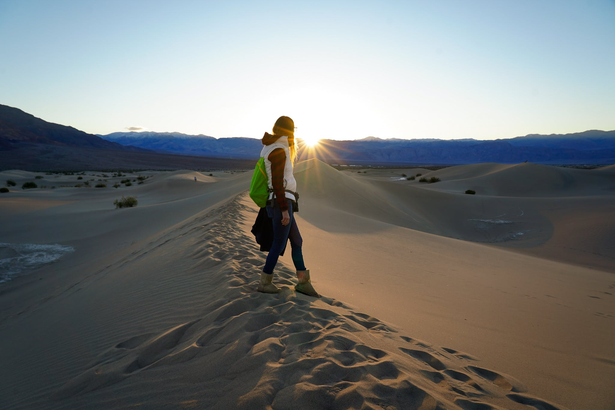 Woman on sand dune at Mesquite Flat at sunset in Death Valley National Park