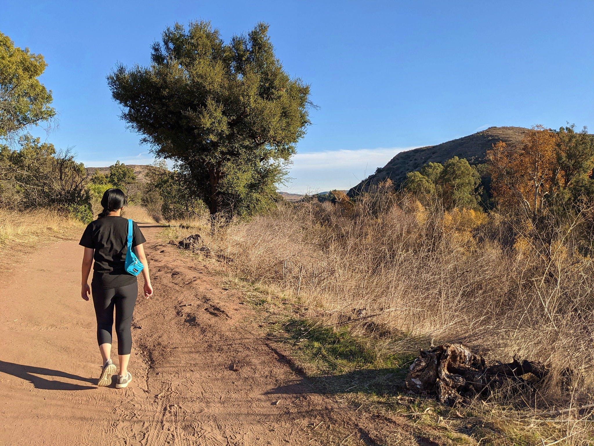 Woman hiking on a trail at Santiago Oaks Regional Park in Orange County