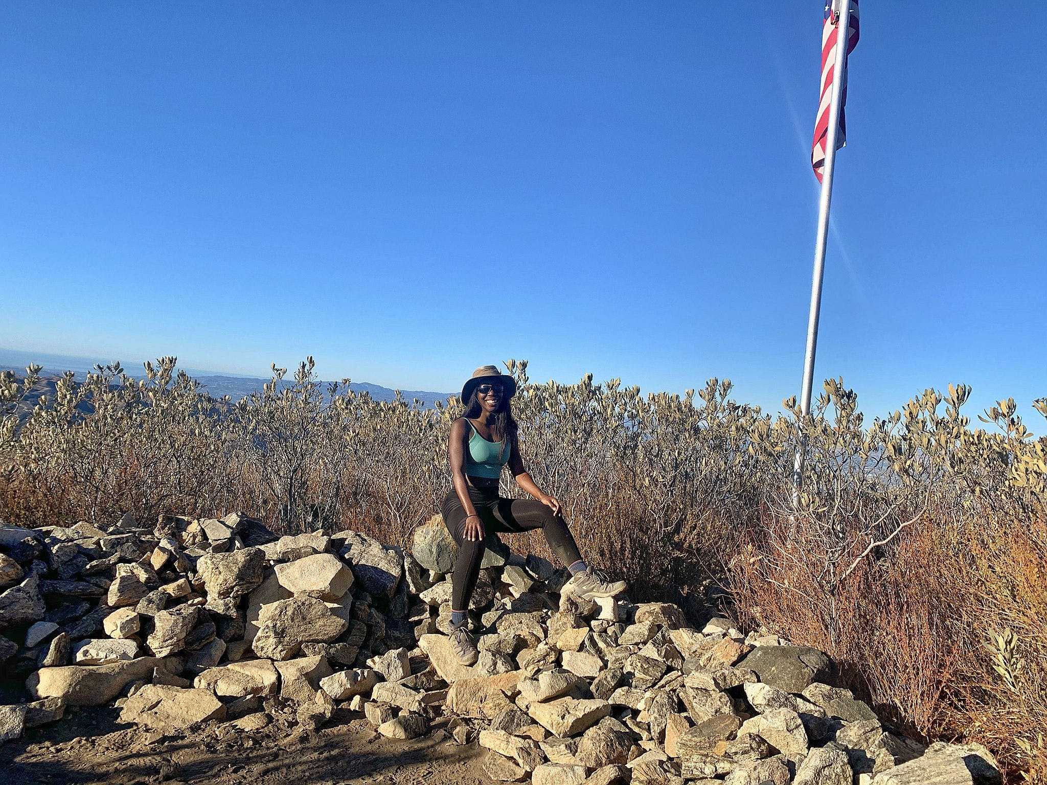 Woman sitting and smiling at the summit of Mount Lukens in Los Angeles
