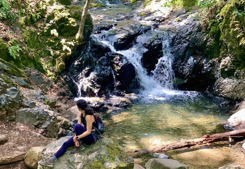 Woman sitting at the base of a waterfall at Uvas Canyon County Park in the Santa Cruz Mountains