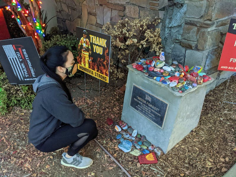 Woman kneeling down to look at an art rock tribute to firefighters in Monrovia