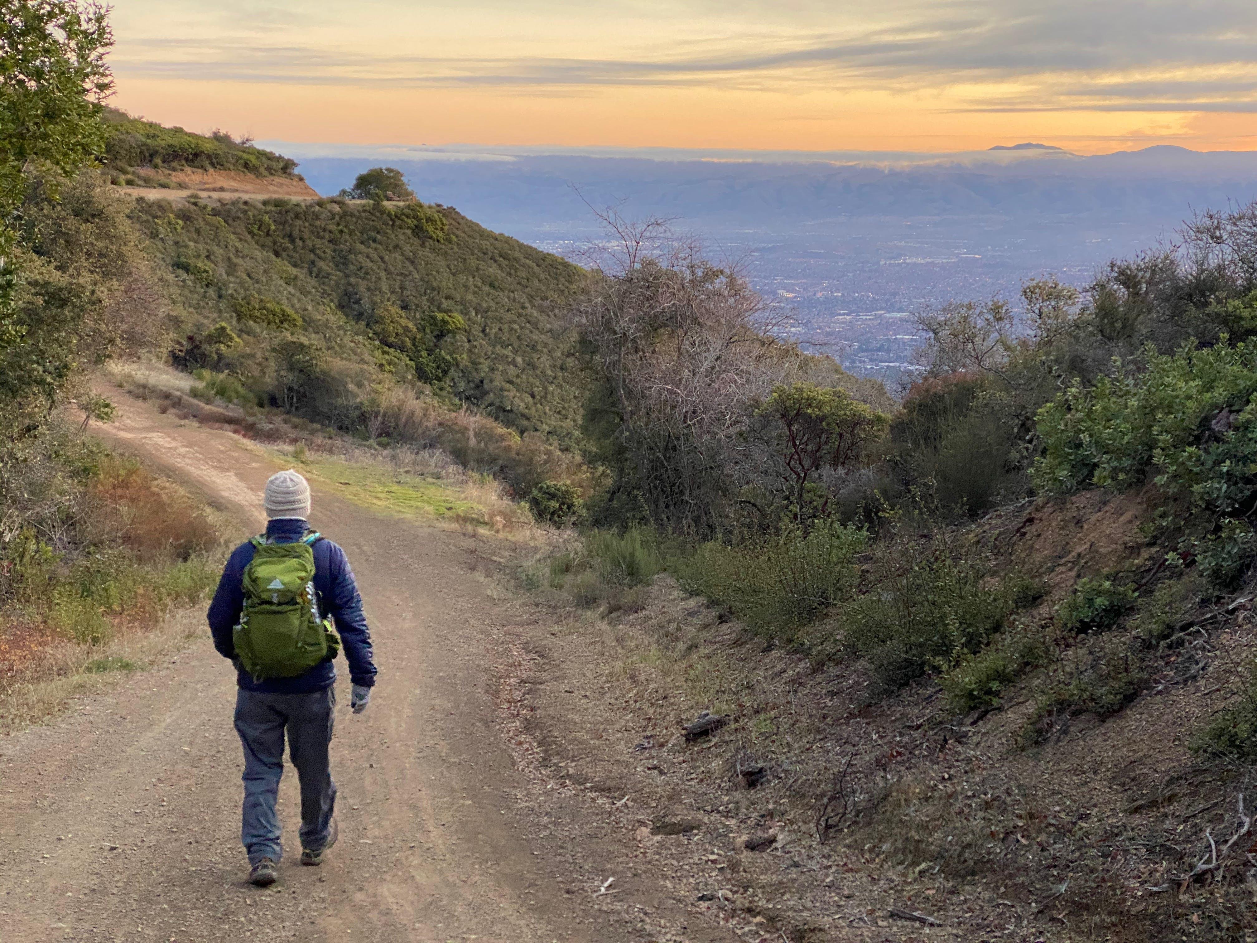 Man hiking the Aquinas Trail at sunrise in the South Bay at El Sereno Preserve
