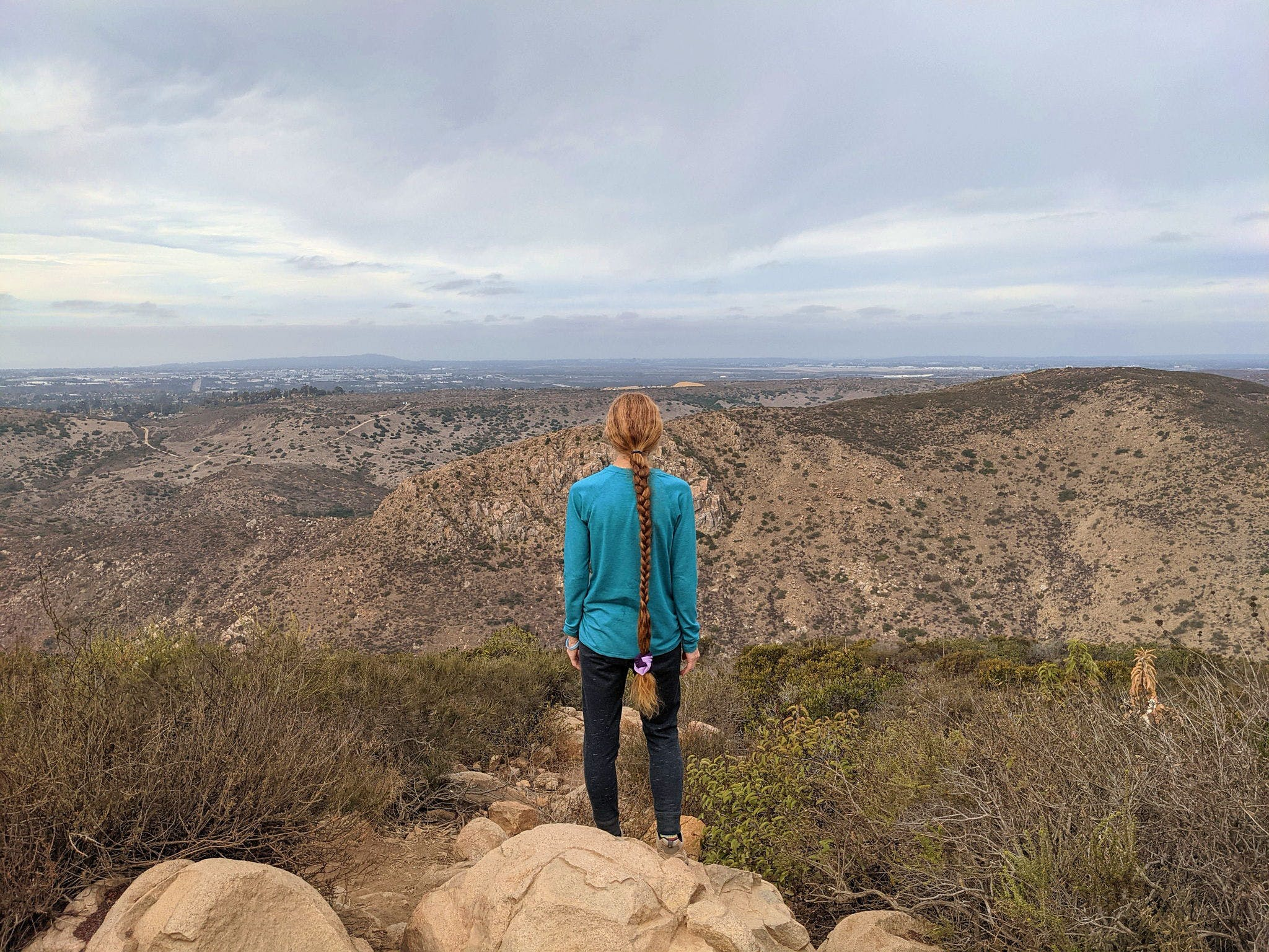 Woman standing at Kwaay Paay peak in San Diego County
