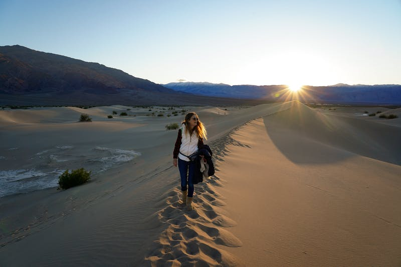 Woman standing on top of a sand dune at Mesquite Flat in Death Valley National Park at Sunset
