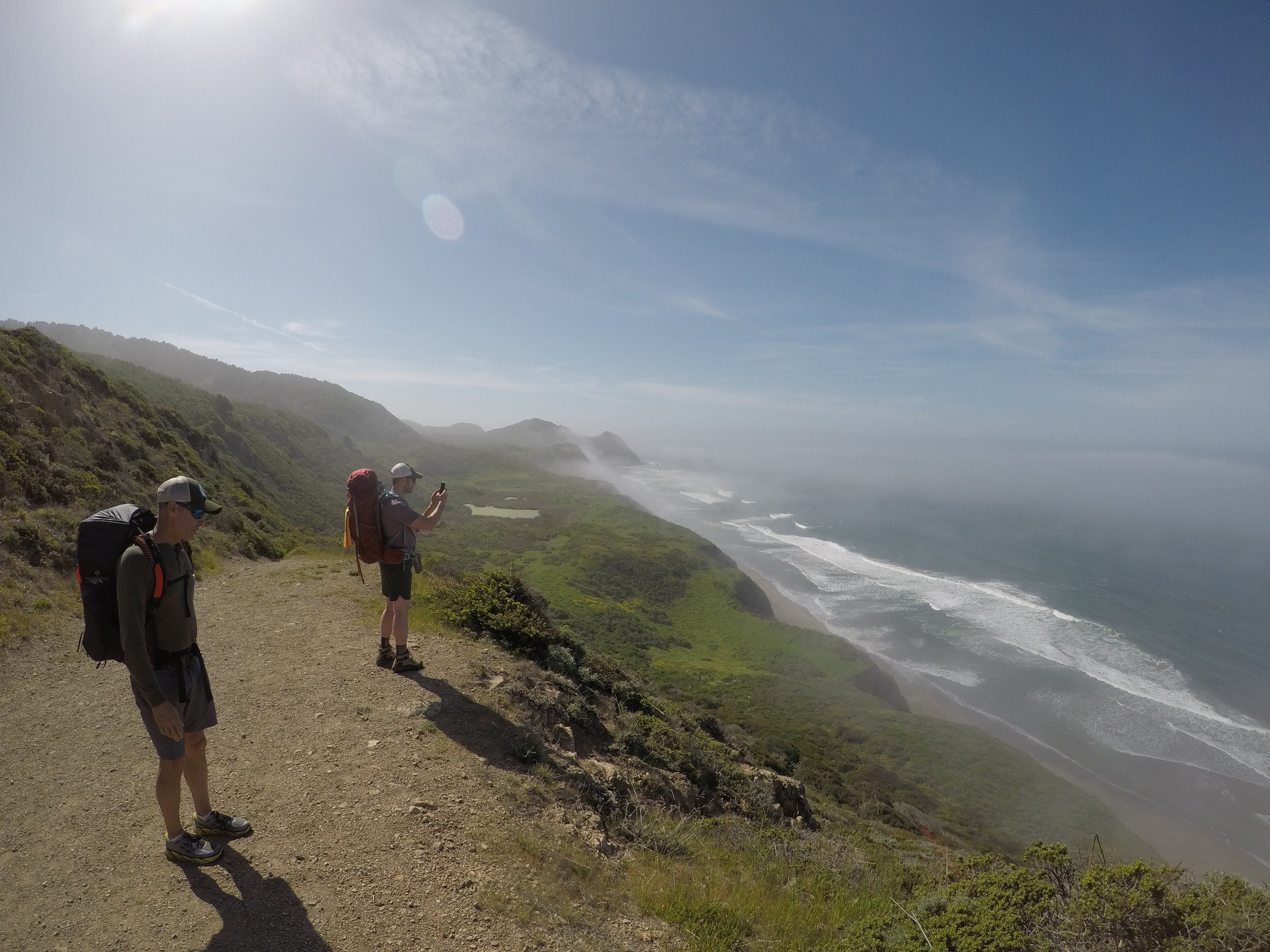 Backpackers overlooking the bluff and down to the Pacific ocean at Point Reyes National Seashore near Wildcat Camp