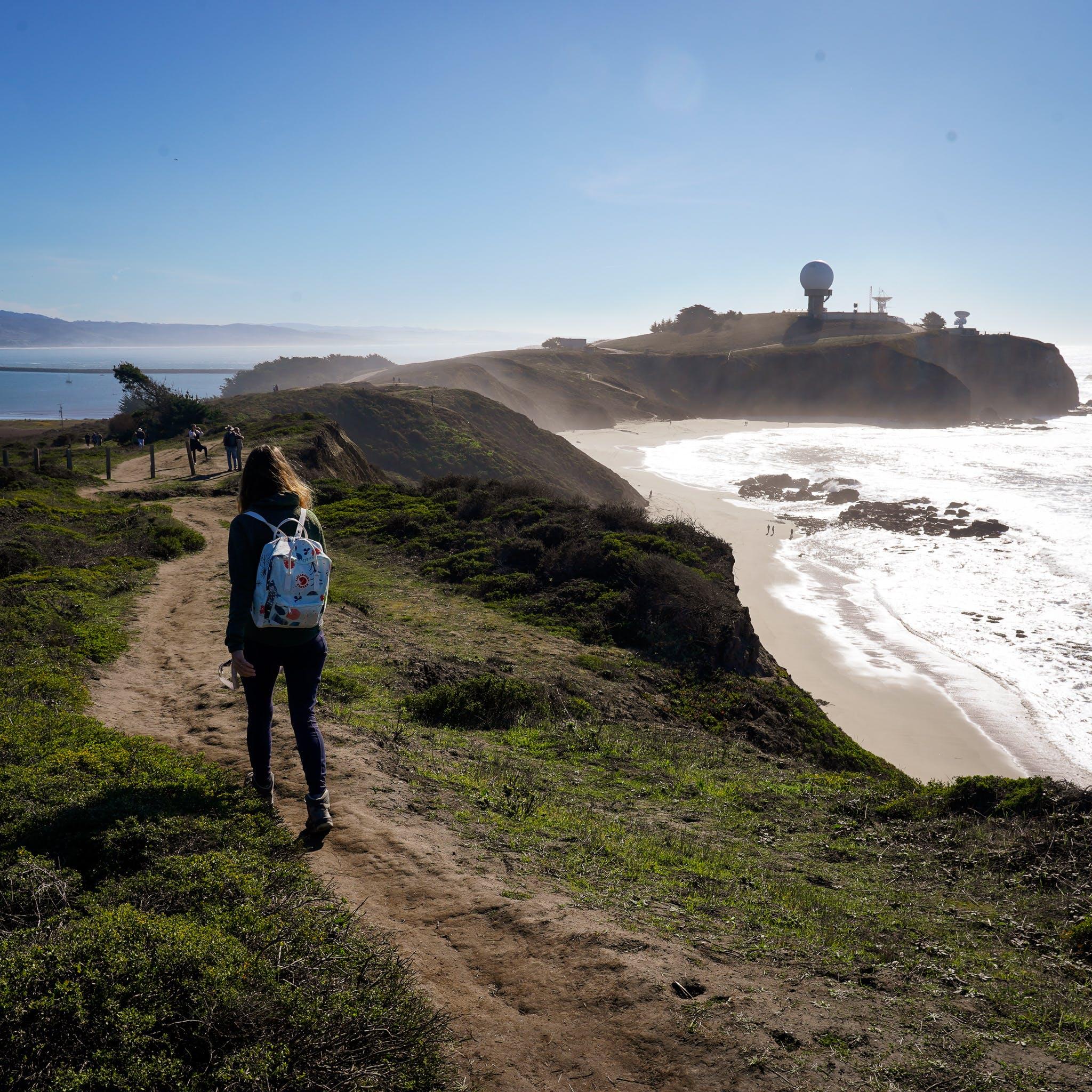 Woman hiking along Pillar Point Bluff towards the Pillar Point Air Force Station