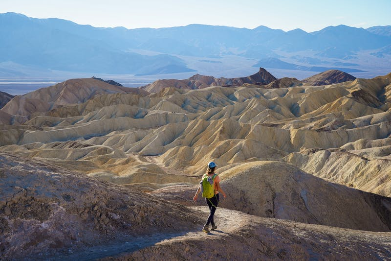 Woman hiking the Badlands Trail in Golden Canyon in Death Valley National Park