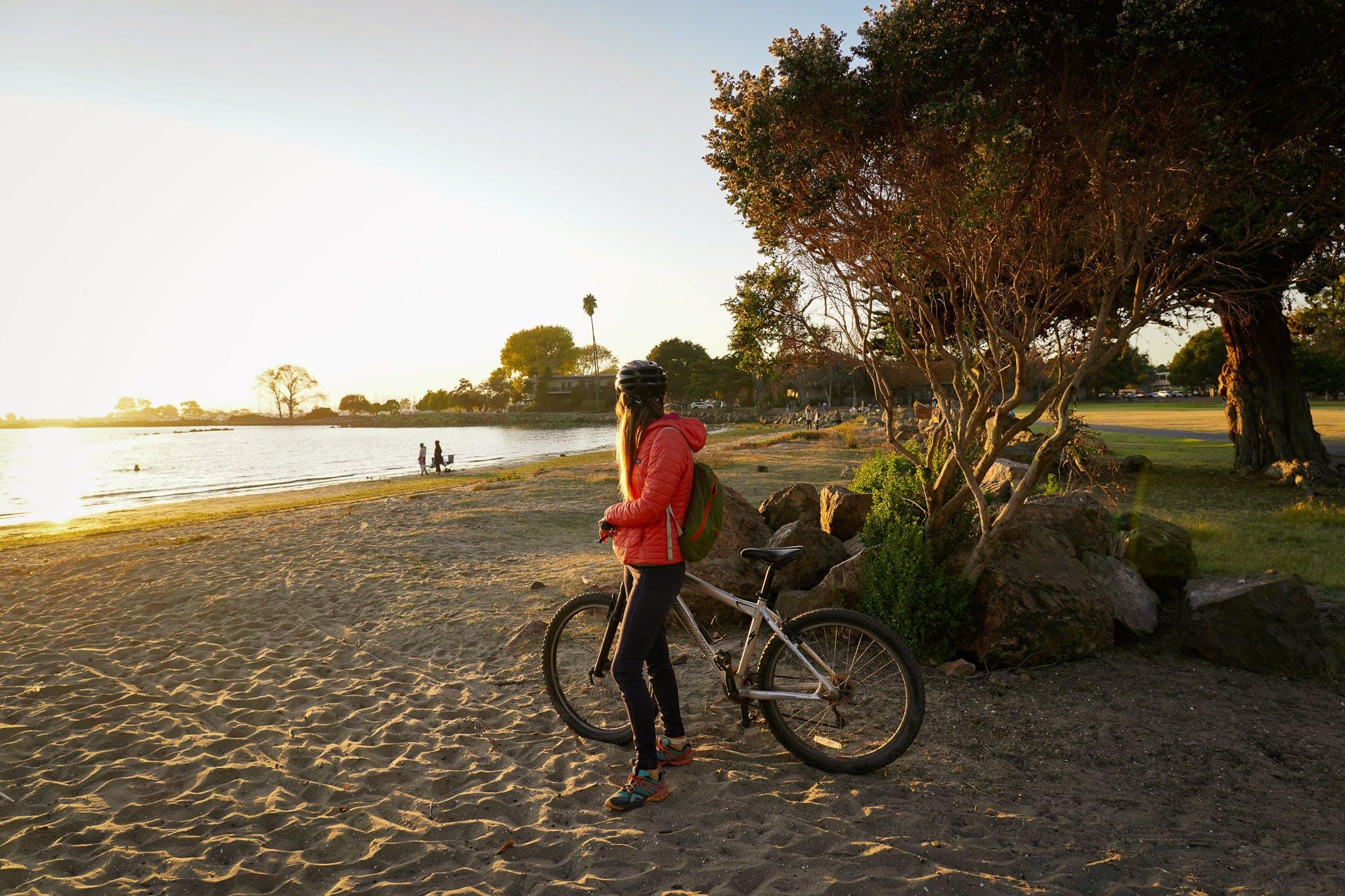 Woman on a bike at a beach in Alameda