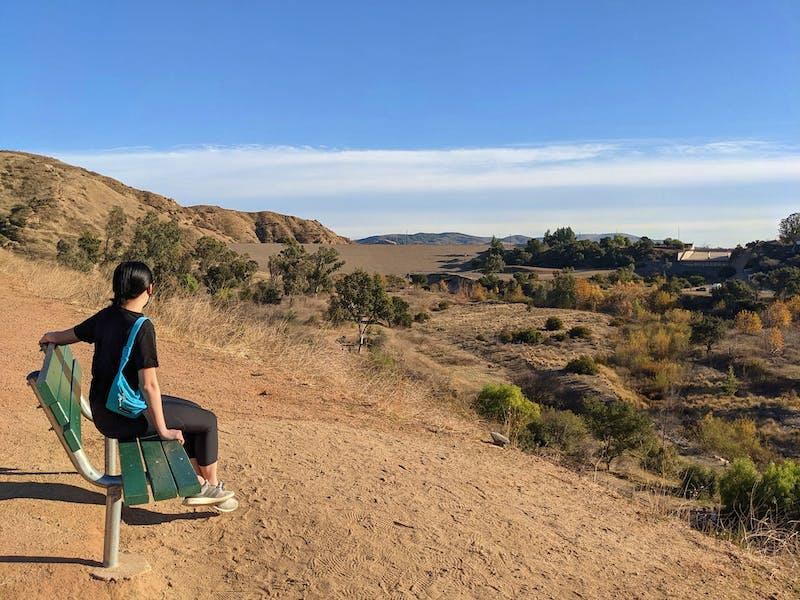 Woman sitting at a bench along a path overlooking Villa Park Dam at Santiago Oaks Regional Park