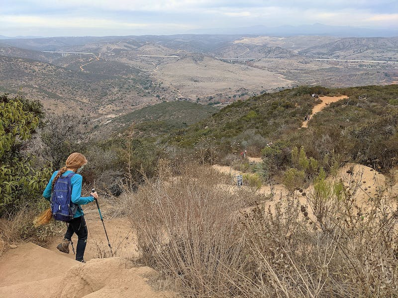 Woman hiking downhill at Kwaay Paay in Mission Trails Regional Park San Diego County