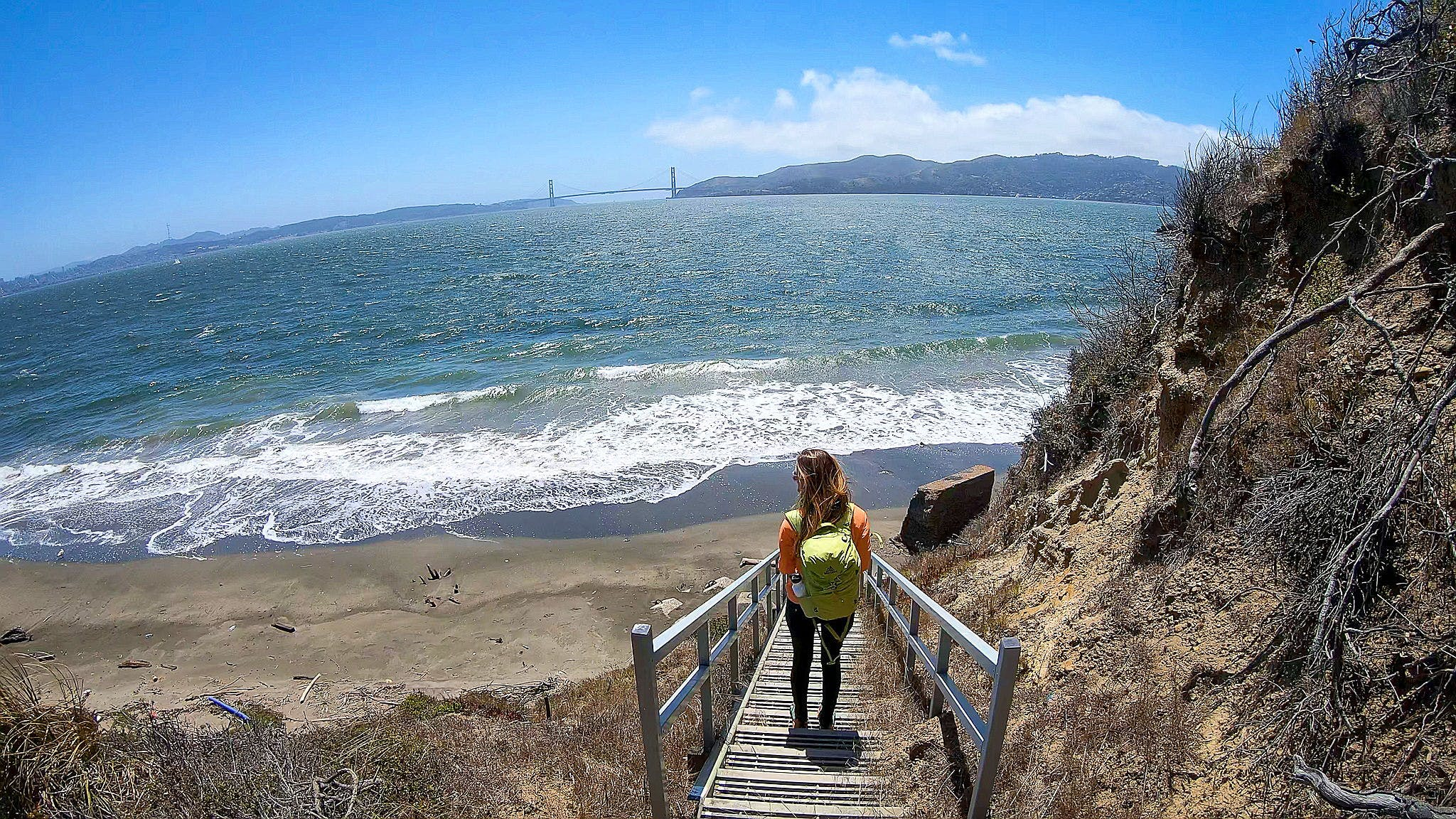 Woman hiking down stairs to Perles Beach on Angel Island State Park in the San Francisco Bay Area