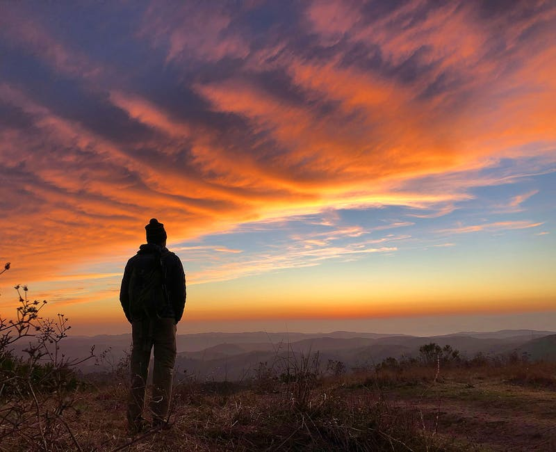 Man standing at Windy Hill and watching a fiery sunset at Windy Hill Preserve
