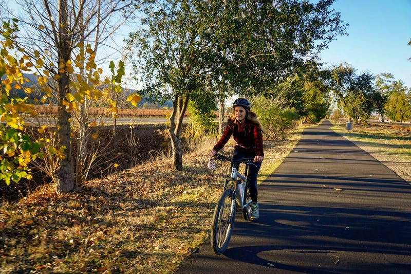 Woman riding a bike on the the Vine Trail in Napa Valley