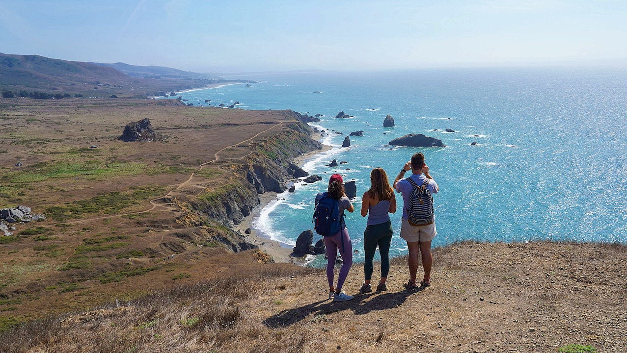 Three people standing at an overlook on the Kortum Trail in Sonoma County