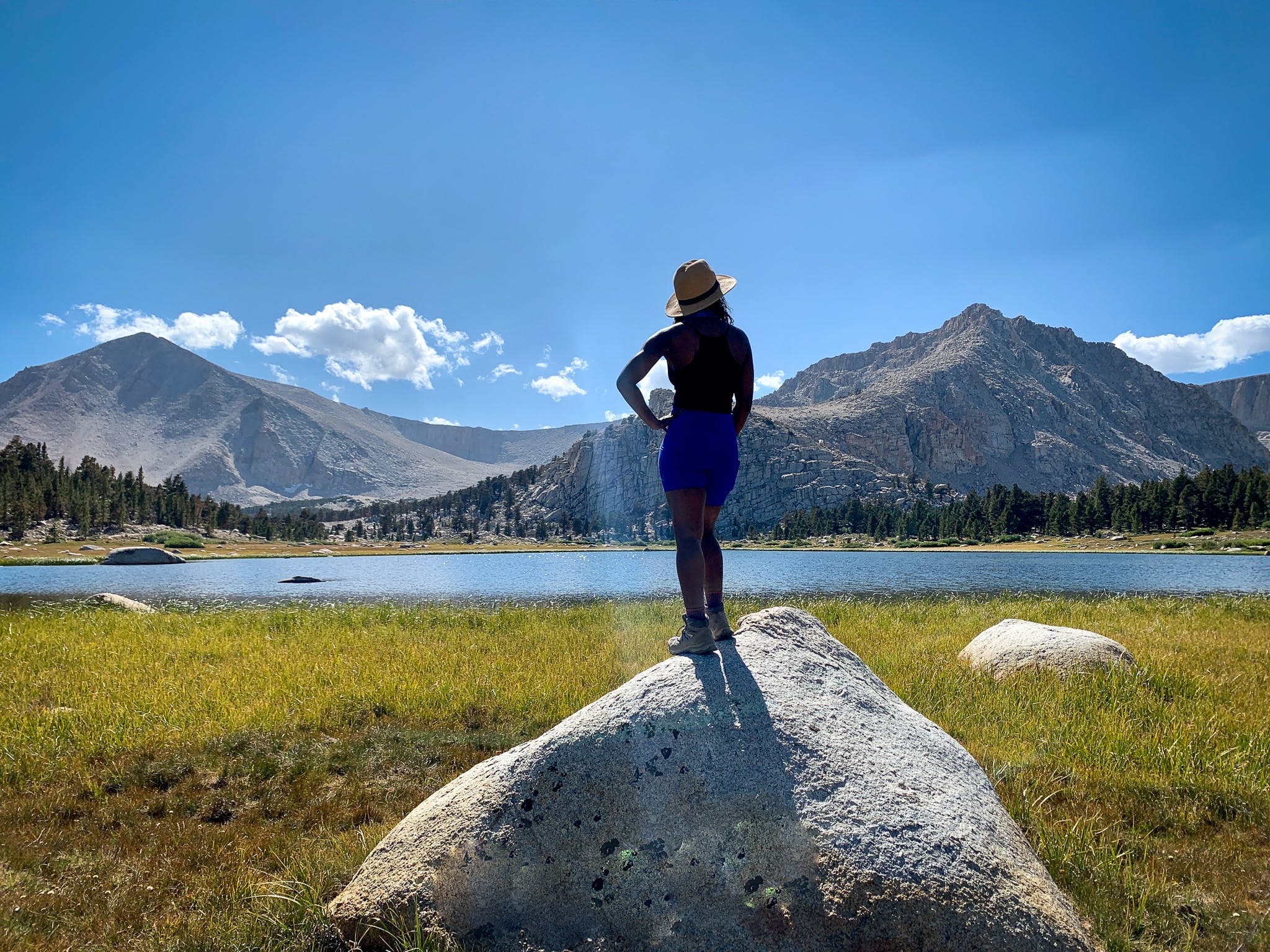 Woman on a large rock overlooking one of the lakes at Cottonwood Lakes in John Muir Wilderness