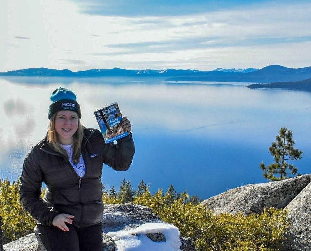 Nicole Szanto author of Tahoe & Reno guidebook, holding up her book in front of Lake Tahoe.