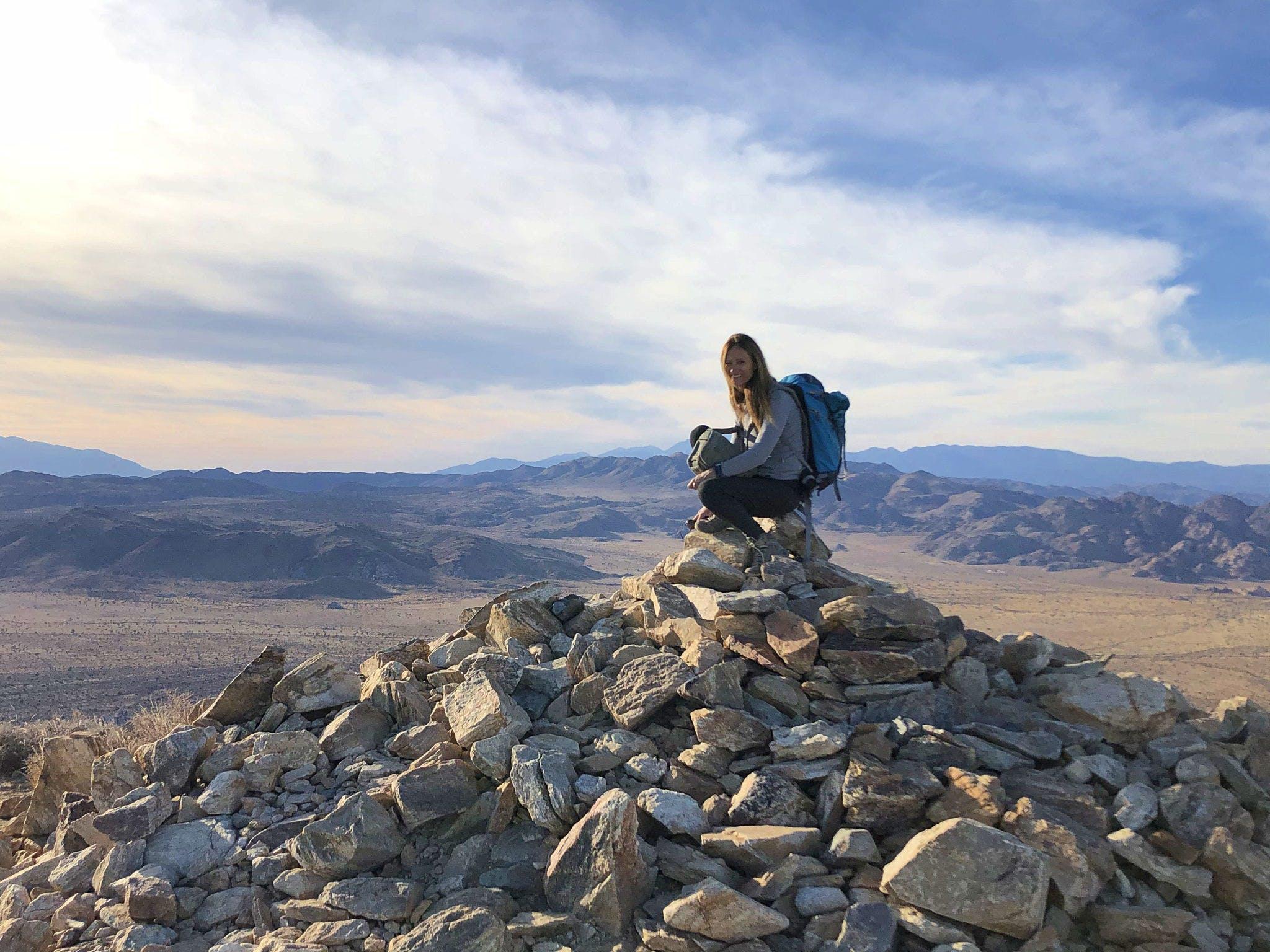 Woman sitting on rock pile at Ryan Peak in Joshua Tree National Park