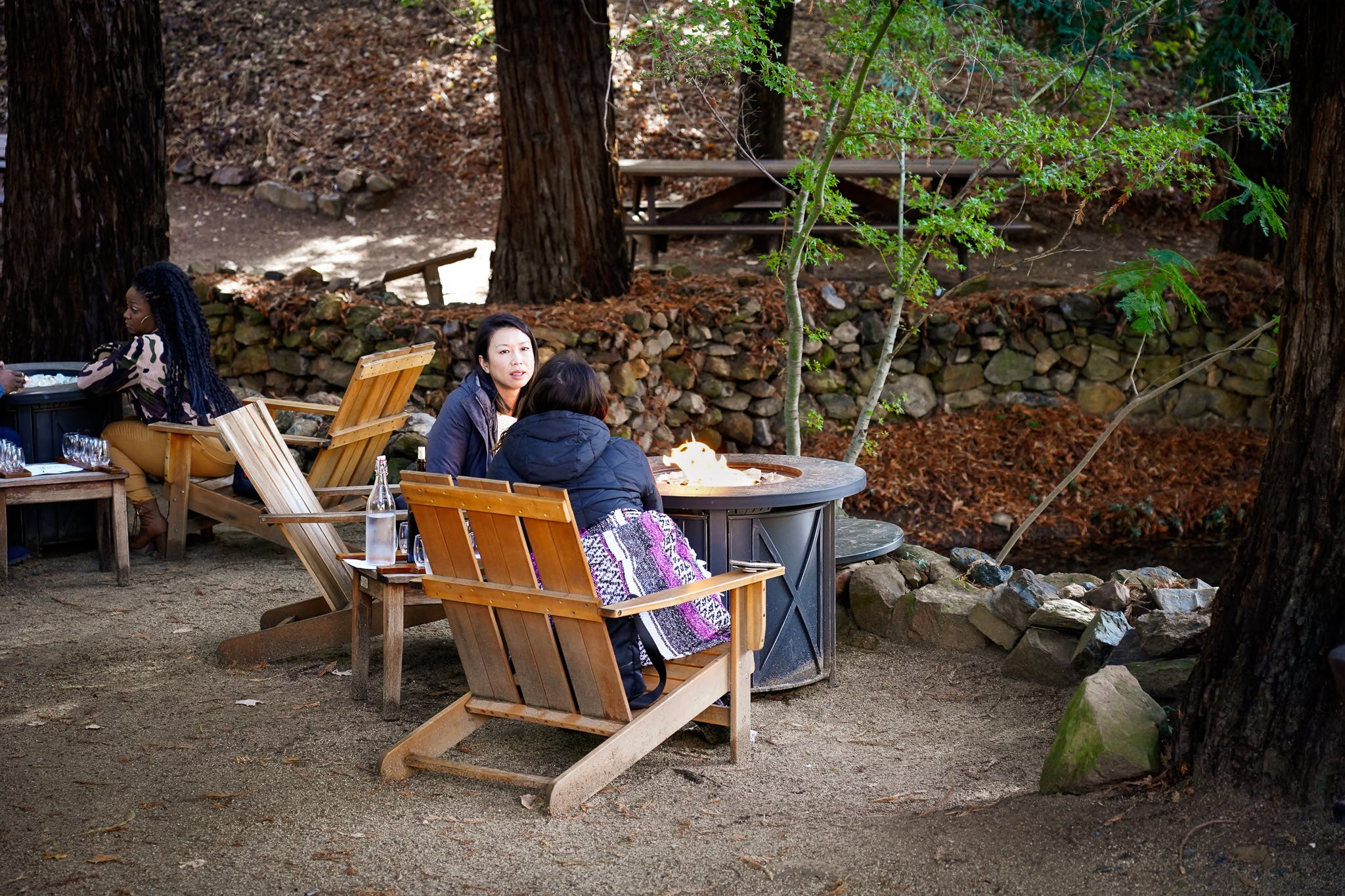 Women enjoying wine around a fire pit at Boeger Winery in Placerville Apple Hill