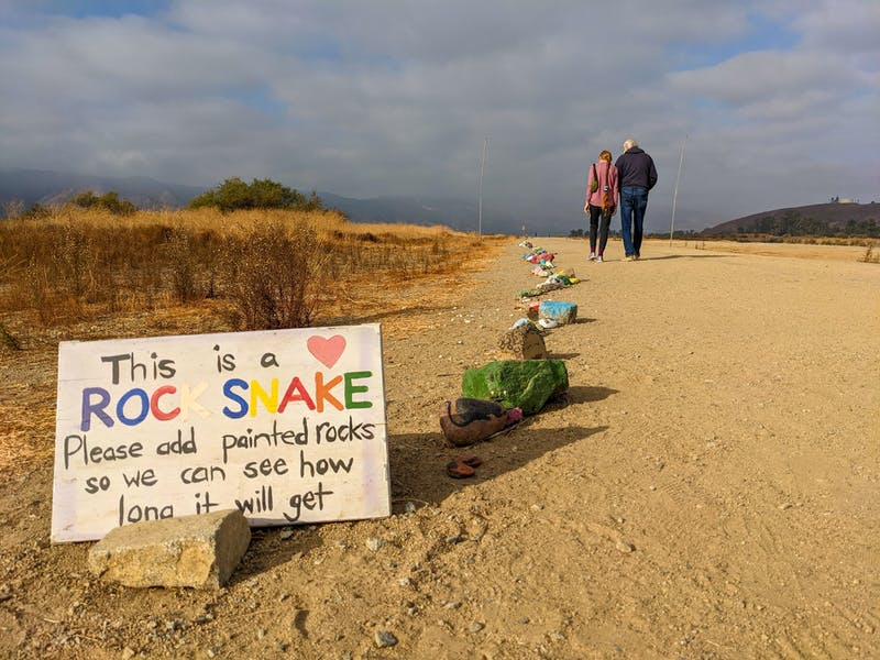 A couple walking the Levee Trail and looking at the painted Rock Snake at Lake Elsinore
