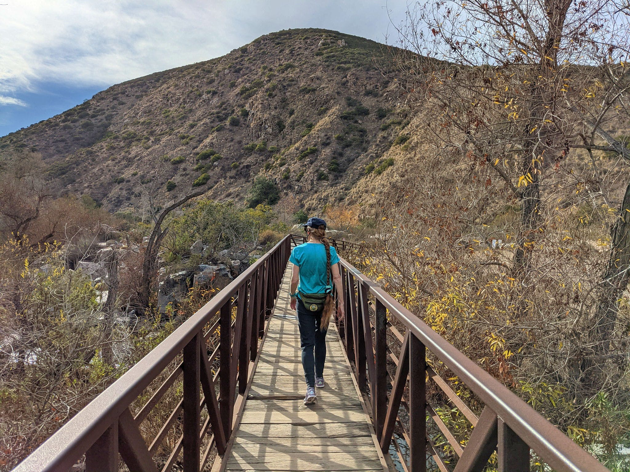 Woman walking over bridge at Mission Trails Regional Park in San Diego