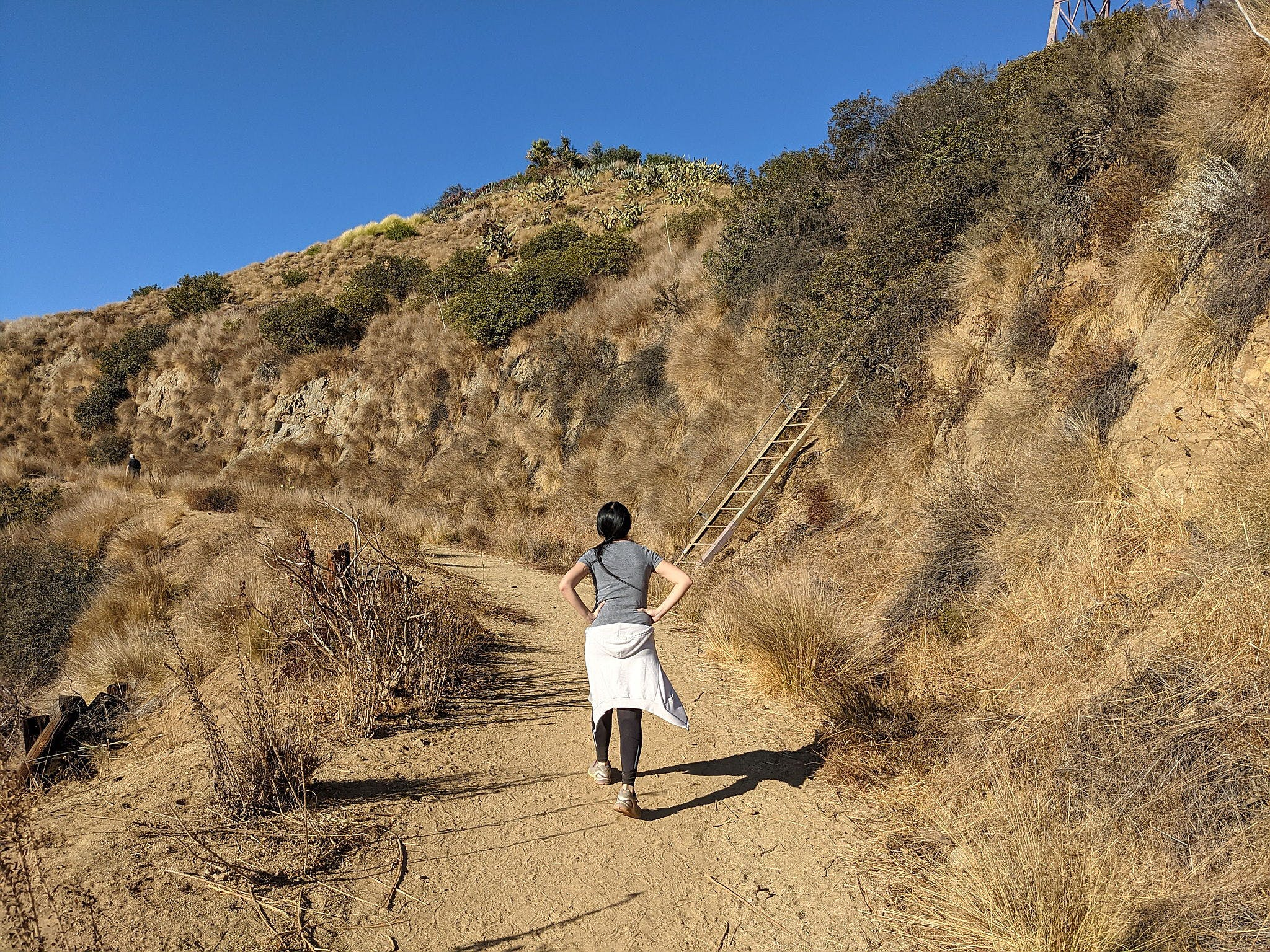 Woman hiking by a ladder on a trail in Trebek Open Space