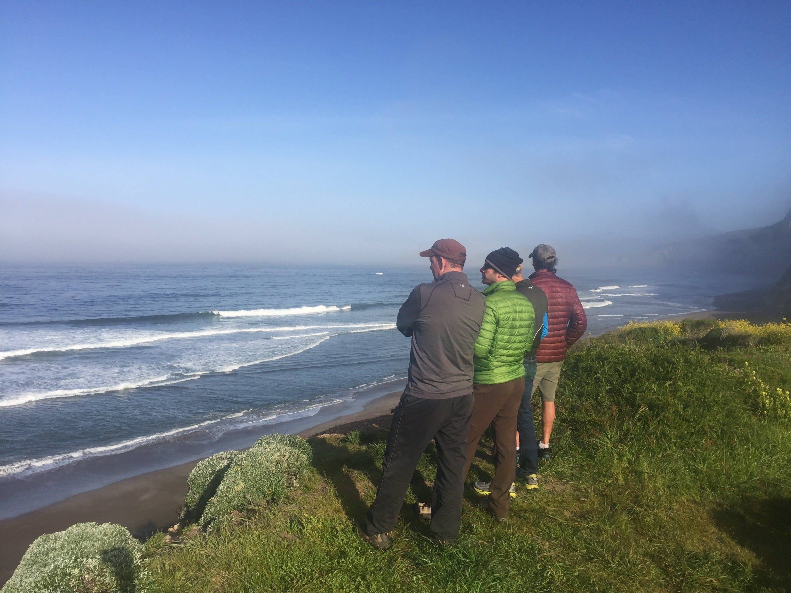 Three friends on the bluff trail at Wildcat Camp overlooking the beach and ocean in Point Reyes National Seashore