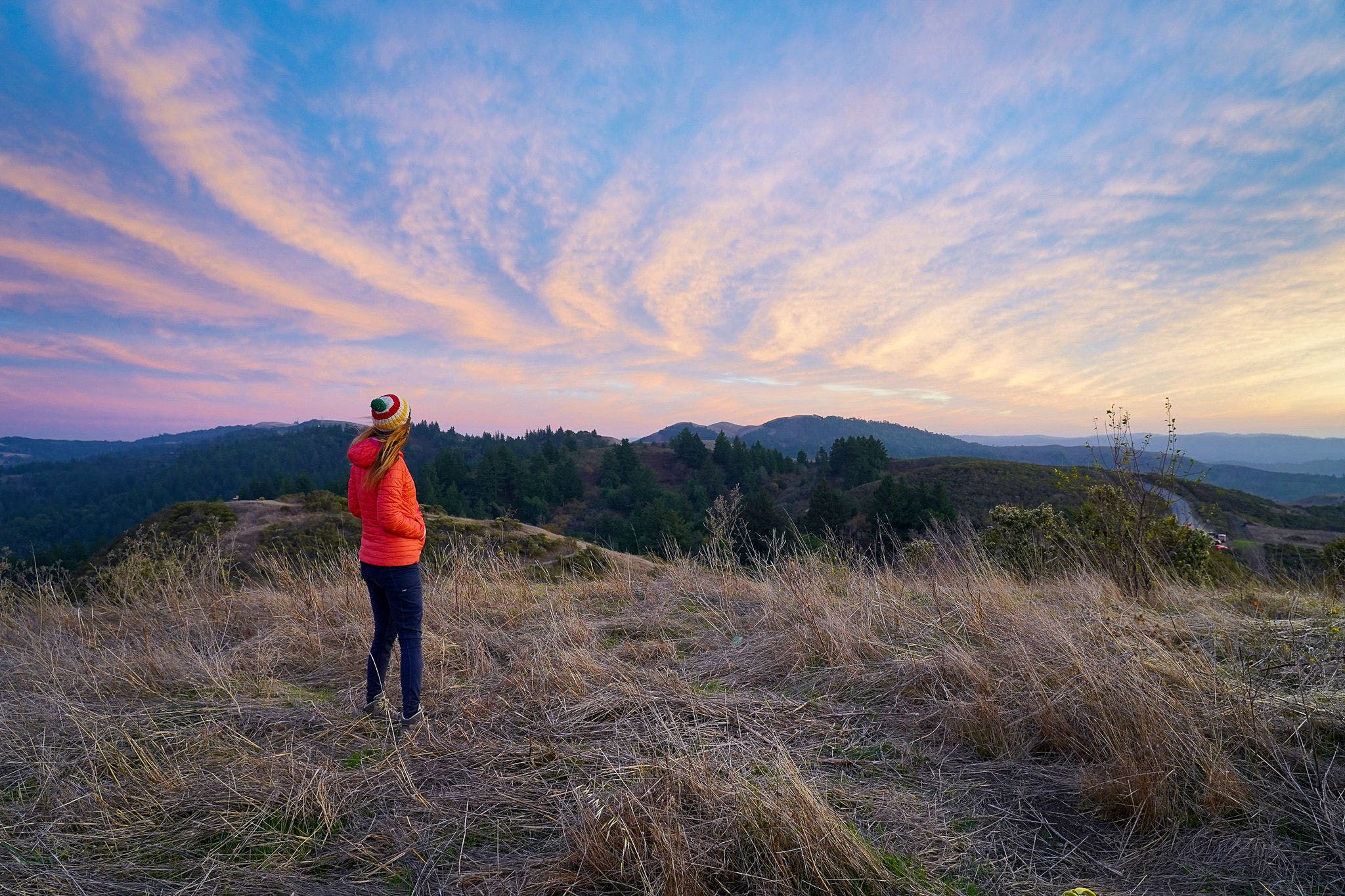 Woman watching a sunset atop Windy Hill at Windy Hill Preserve on the Peninsula