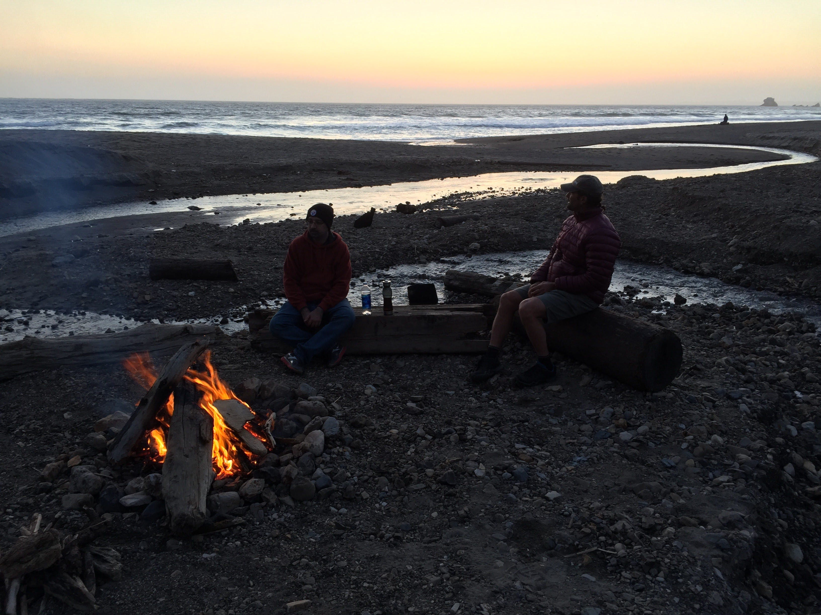 Two people sit around a campfire located at the beach near Wildcat Camp in Point Reyes National Seashore