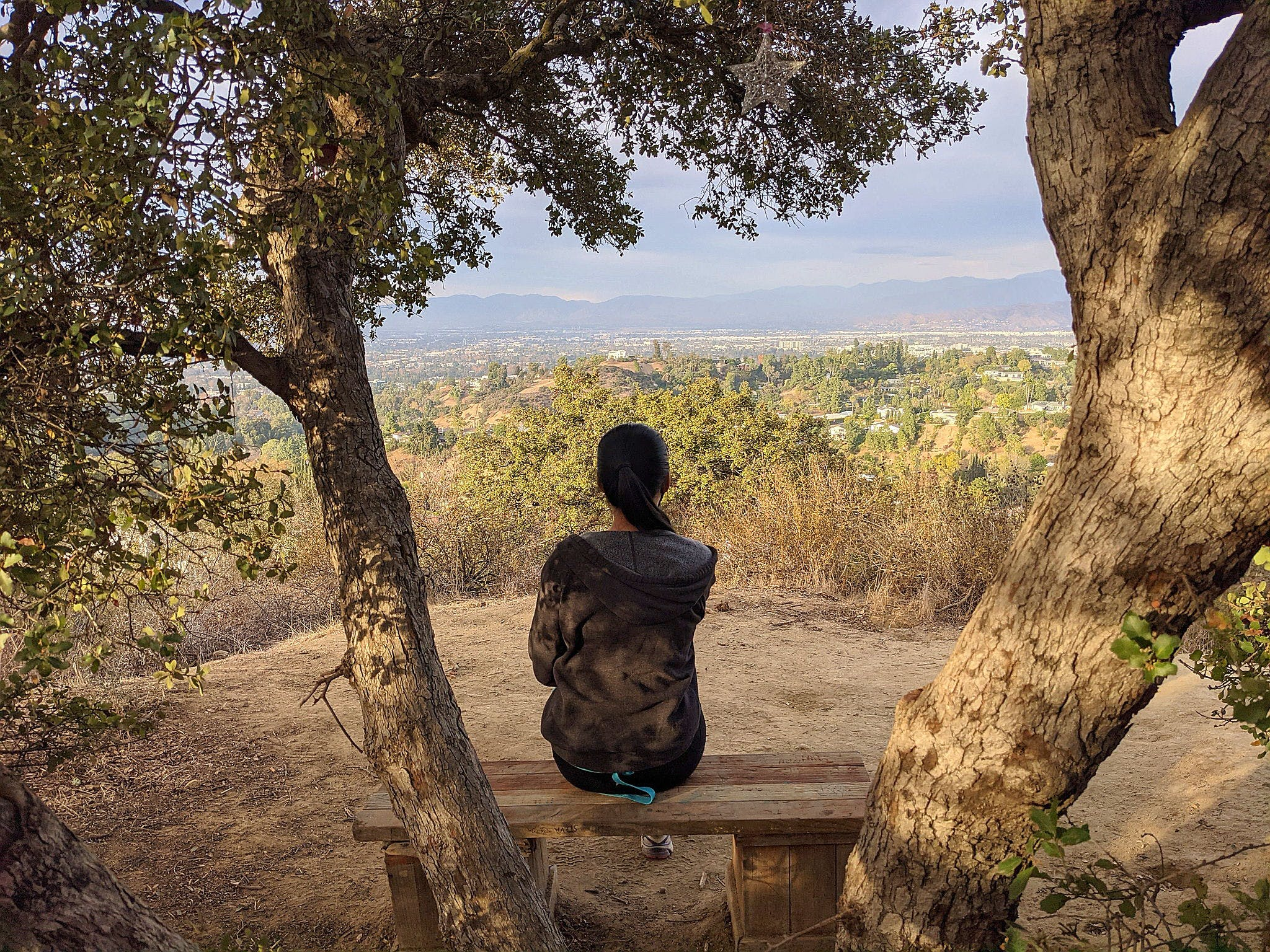 Woman sitting at bench in Fryman Canyon overlooking the San Fernando Valley view