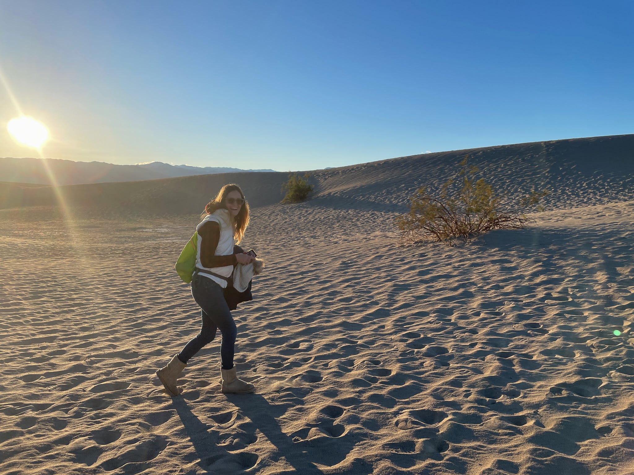 Woman walking to a sand dune at Mesuqite Flat Sand Dunes in Death Valley