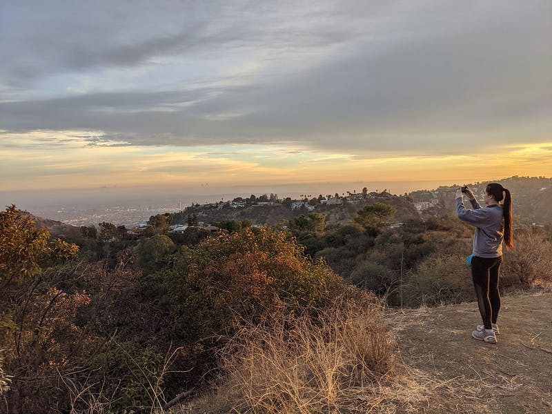 Woman standing and taking a phone photo of the view at Briar Summit Preserve in Los Angeles