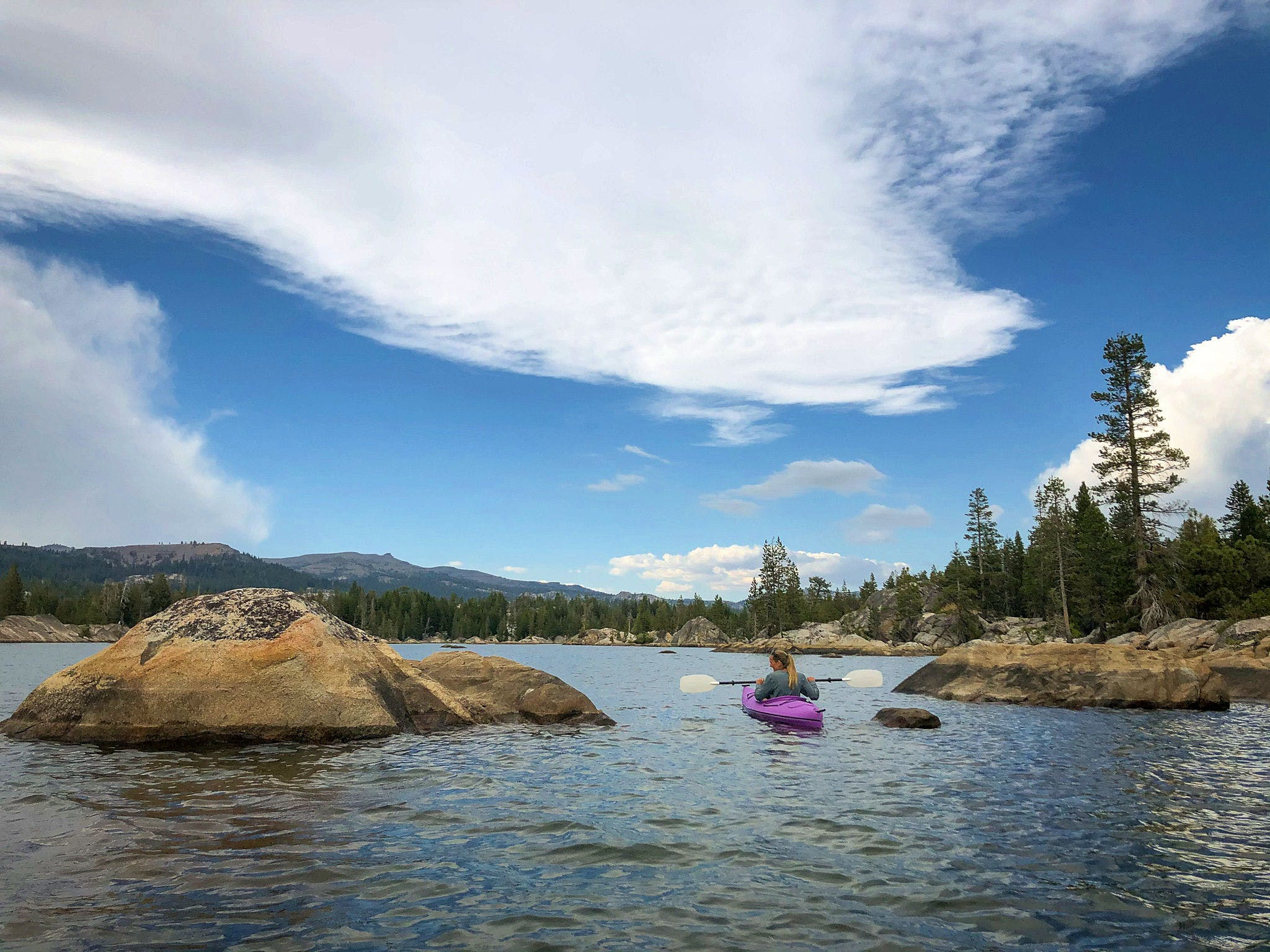 Woman kayaking at Utica Reservoir in Stanislaus National Forest