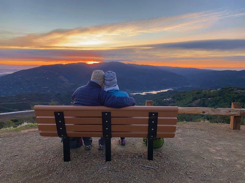 Couple sitting at a bench overlooking the Santa Cruz mountains at sunrise at El Sereno Preserve in the South Bay