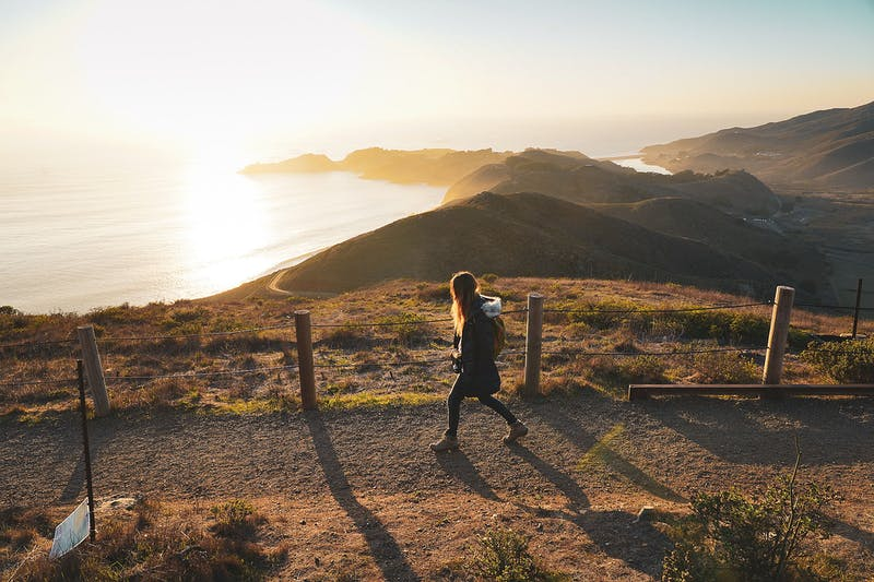 Woman walking trail overlooking the Pacific Ocean at Hawk Hill in Marin County