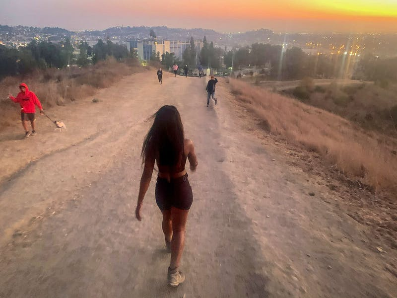 Woman hiking on wide trail overlooking downtown Los Angeles at Ascot Hills in Southern California