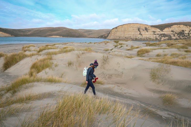 Woman walking on wide open beach in Pescadero
