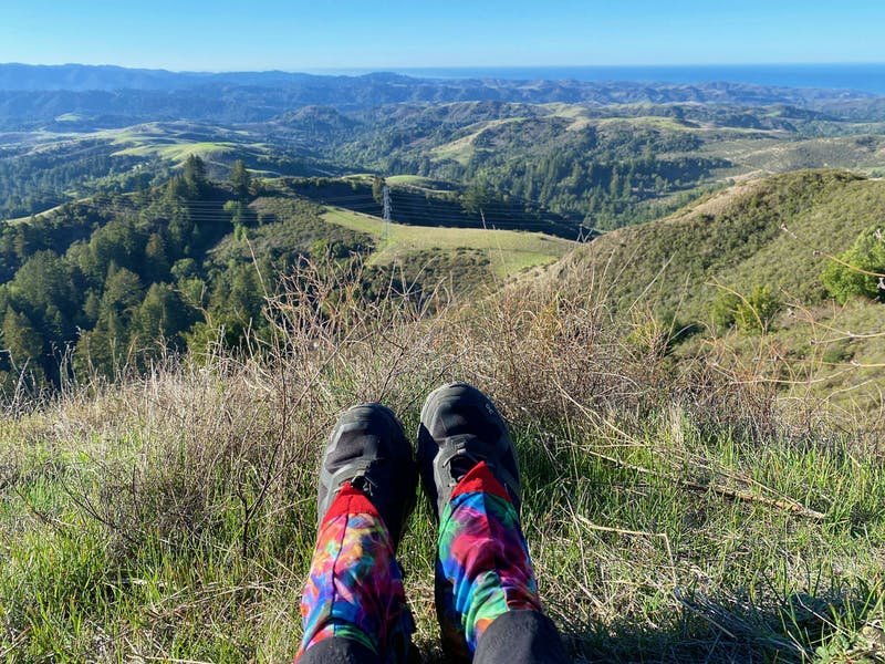 Hiking shoes pictured on person sitting at an overlook of the Santa Cruz Mountains at Upper La Honda Creek Preserve in the South Bay