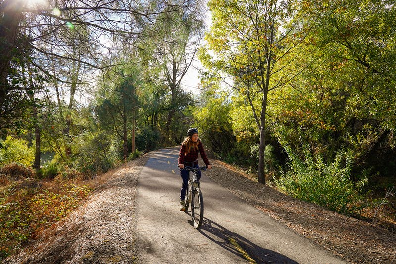 Woman biking on the El Dorado Trail in Placerville