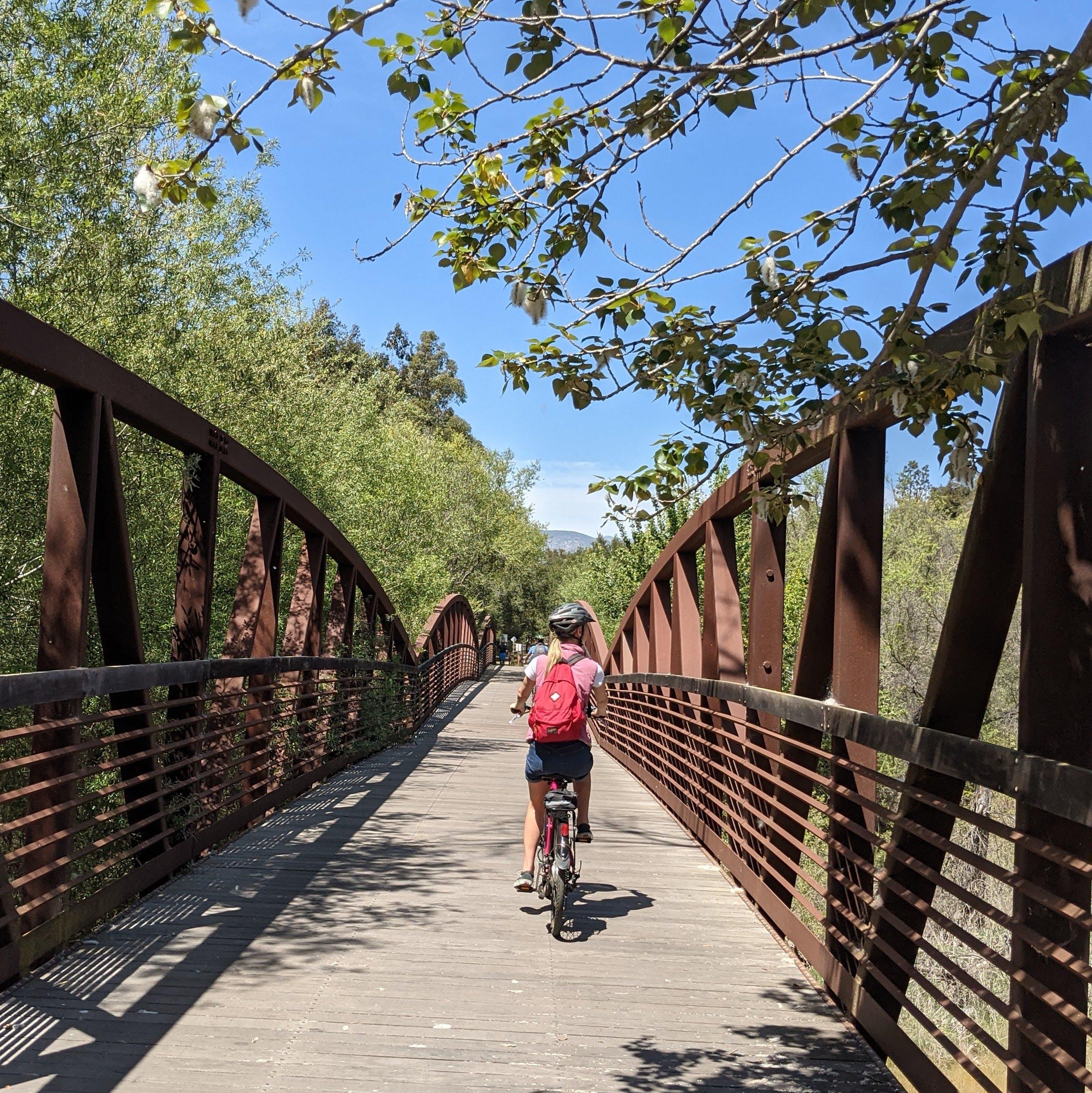 Woman riding her bike over a bridge on the Ventura to Ojai bike path