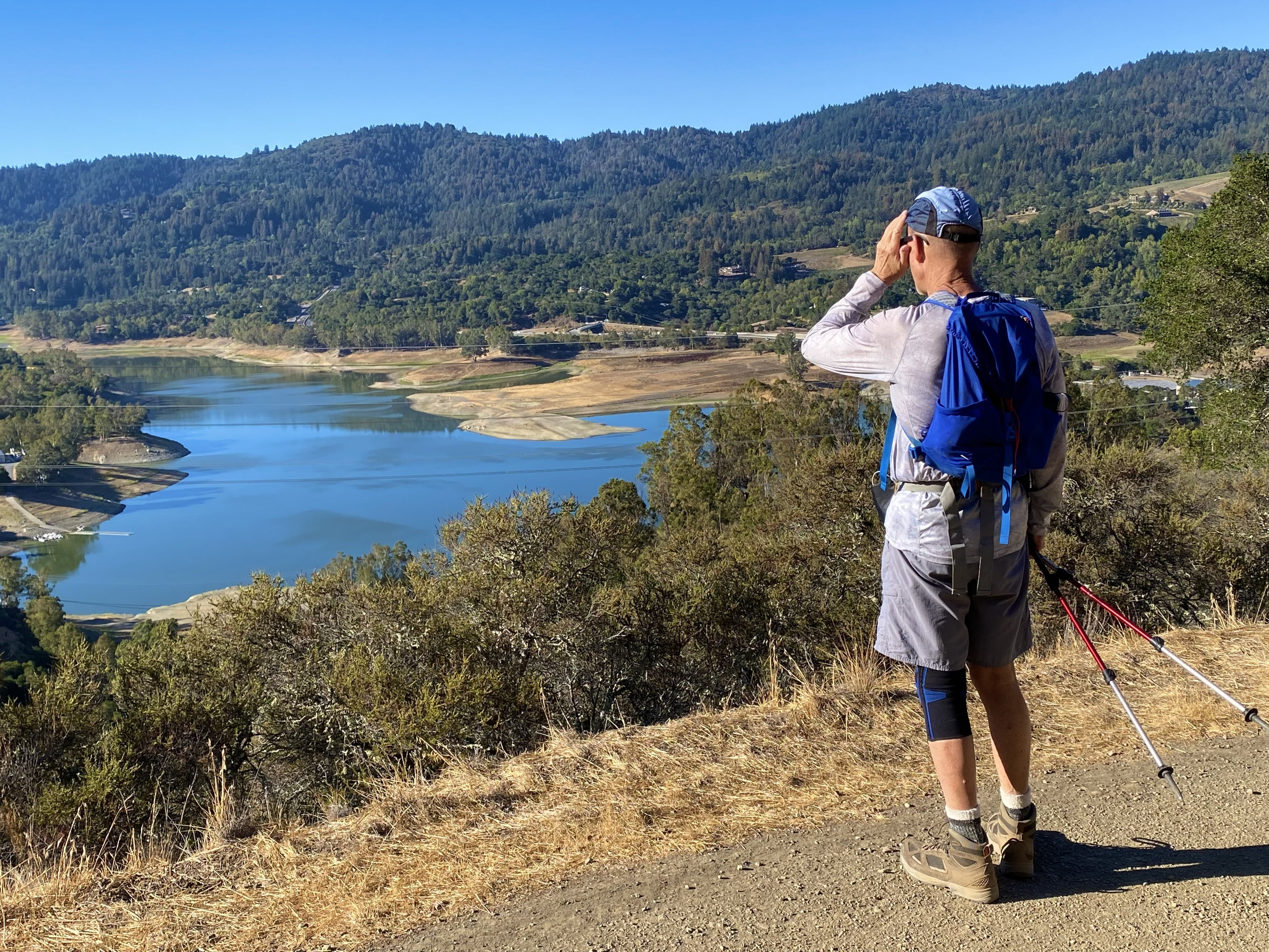 Hiker looking out to the Lexington Reservoir from the high point of St. Joseph's Hill in Los Gatos