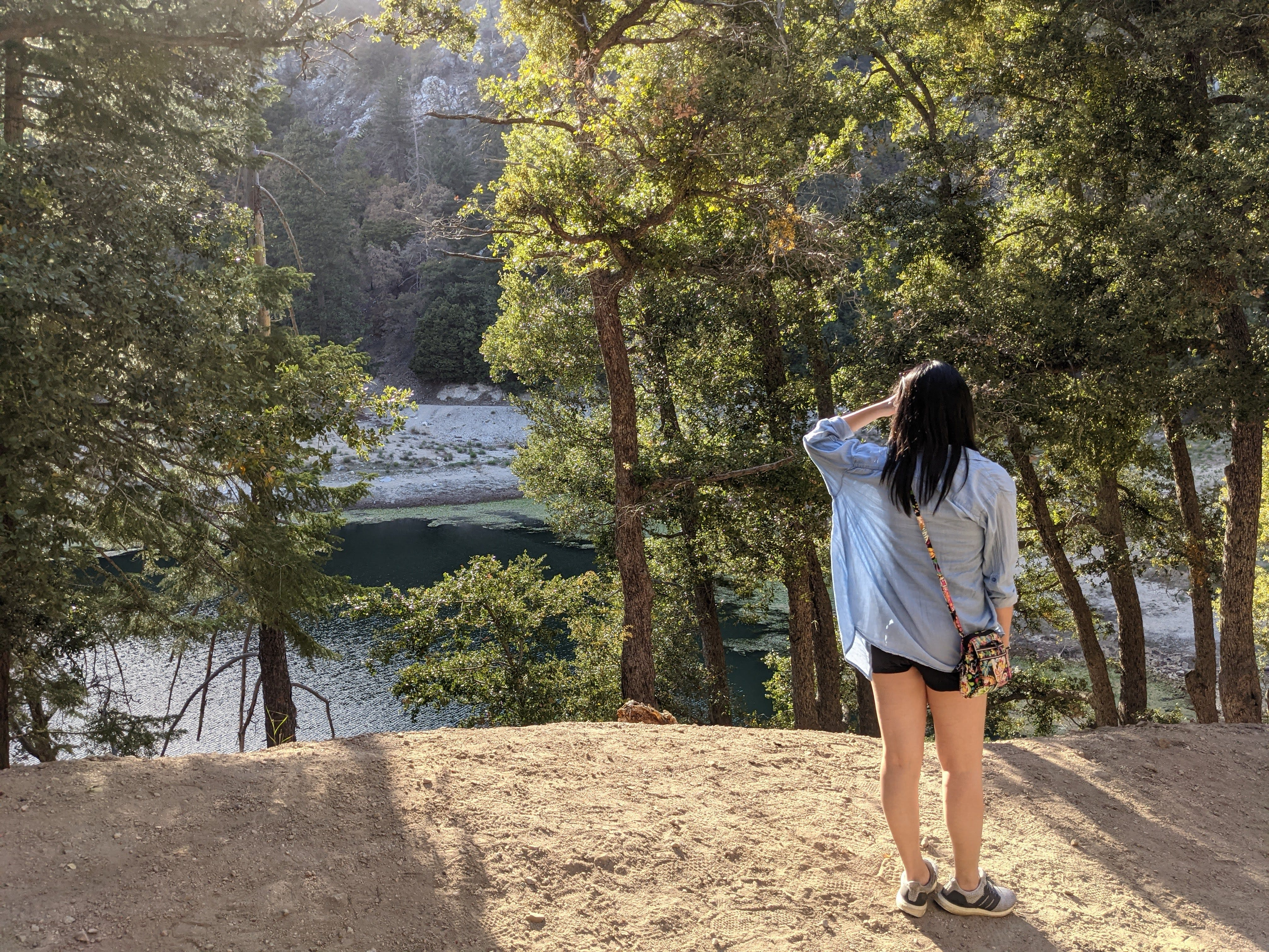 Woman staring out at Crystal Lake in Crystal Lake Recreation Area in Angeles National Forest Southern California