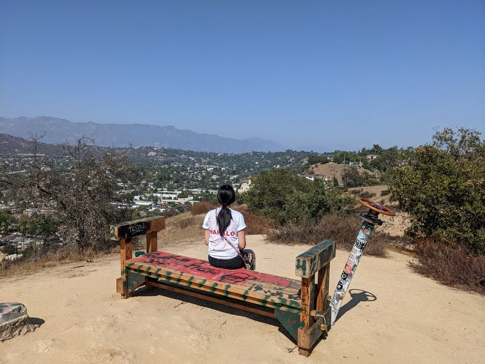 Hiker sitting at bench at summit of Fiji Hill in Los Angeles