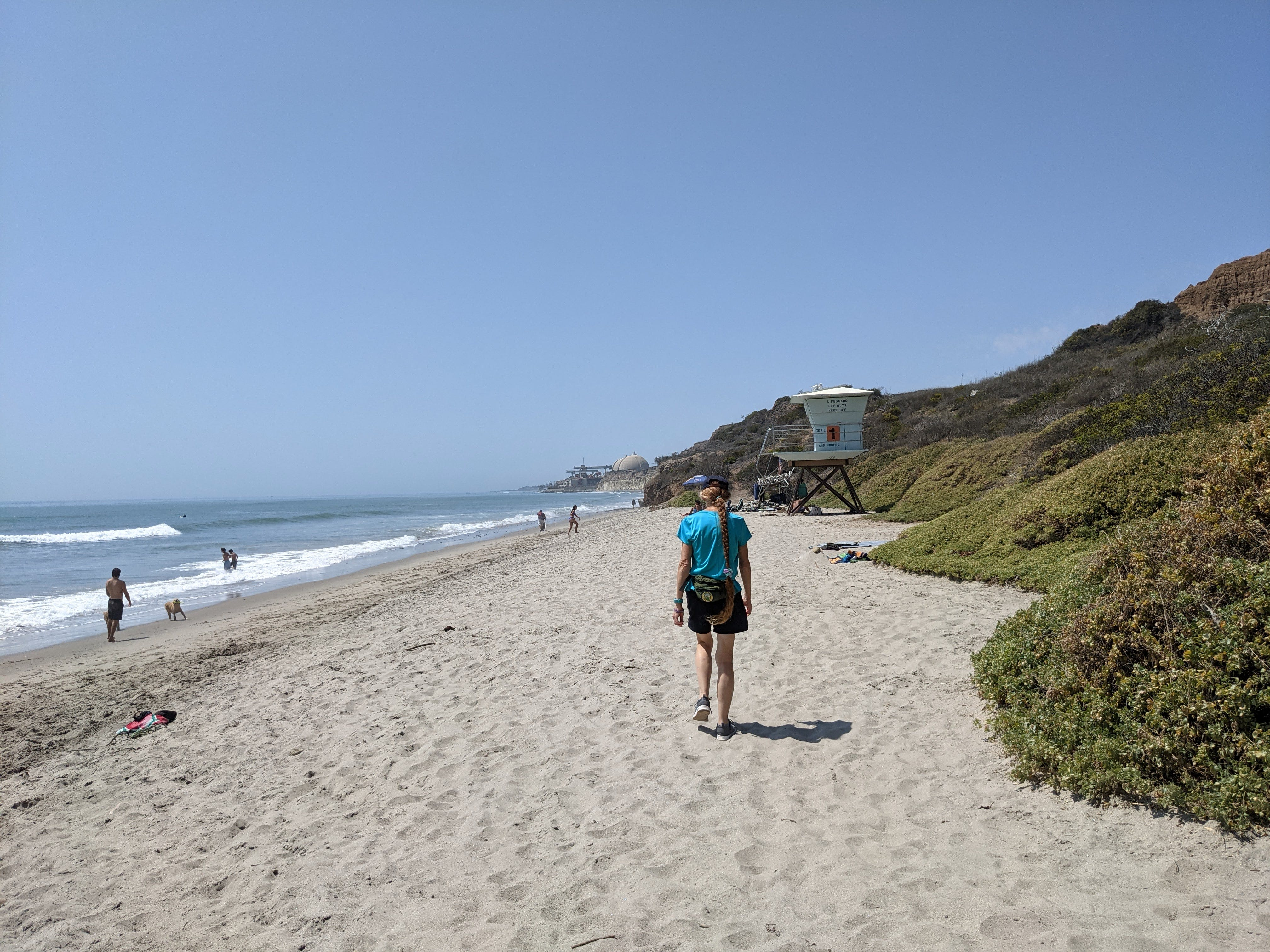 Woman walking along the sand towards a lifeguard tower on San Onofre State Beach in San Diego County