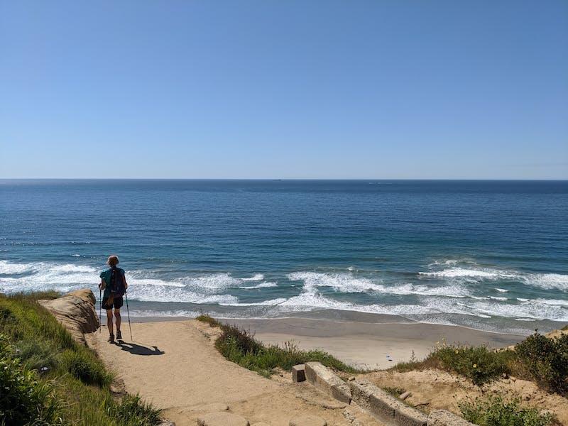 Woman hiking to Black's Beach in La Jolla San Diego