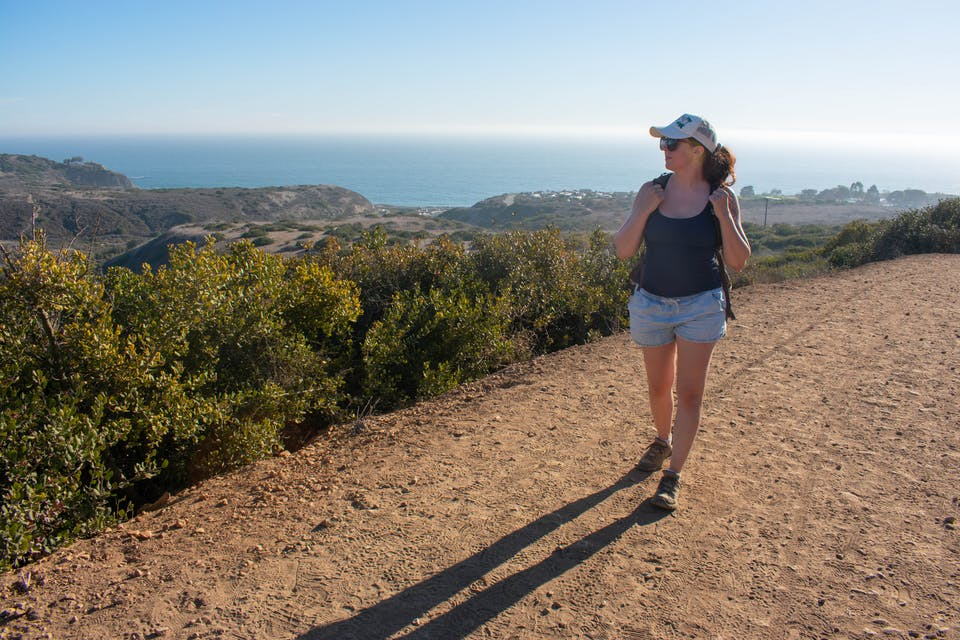 Woman walking on a backcountry hiking trail overlooking the Pacific at Crystal Cove State Park in Orange County