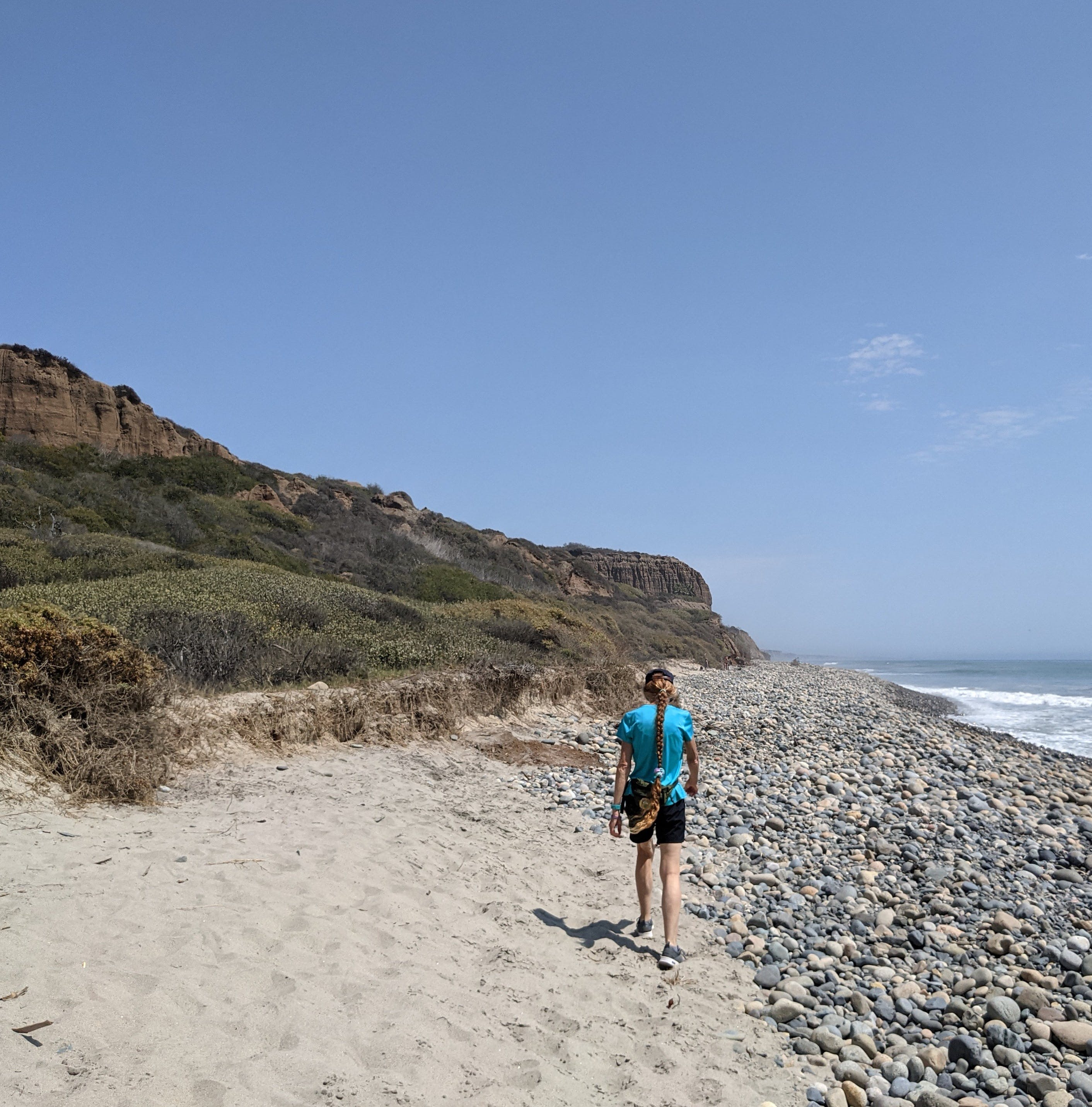 Woman walking on the sandy beach next to a rocky section on San Onofre State Beach in San Diego County
