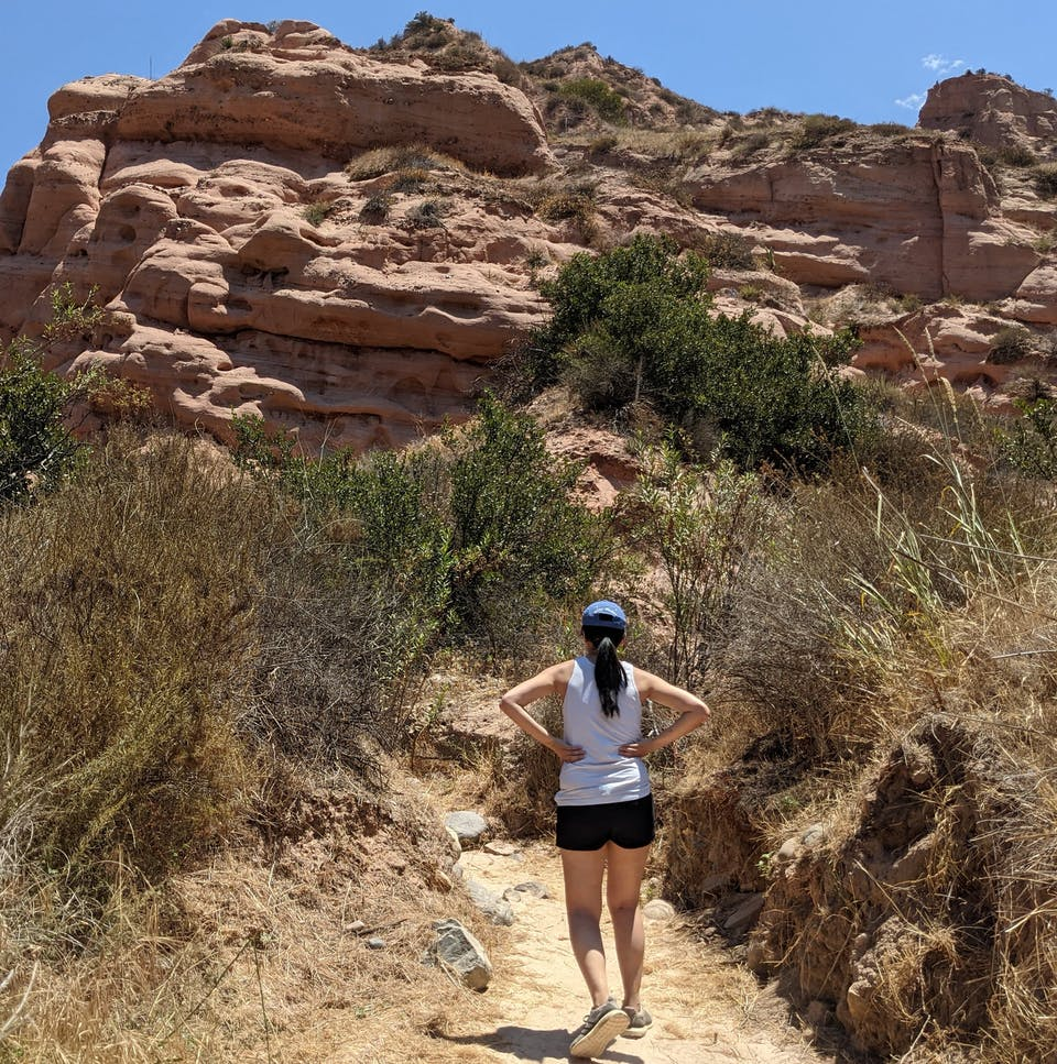 Woman standing on a hiking trail staring at giant red rock formation in front of her at Whiting Ranch Wilderness Park in Orange County