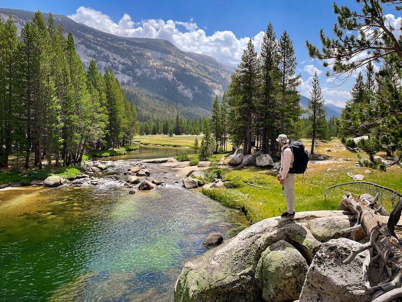 Backpacker on Tuolumne River in Yosemite High Sierra