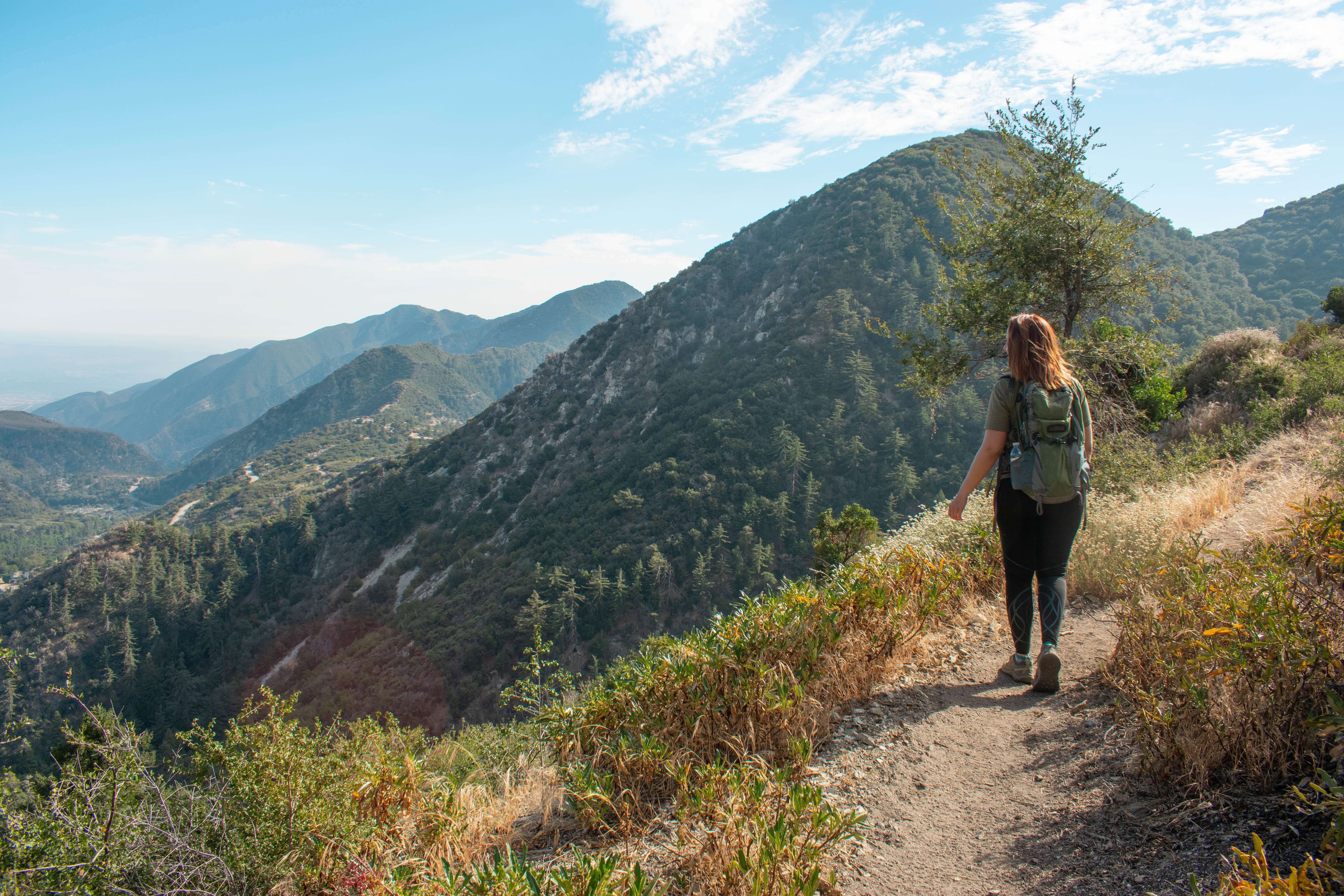 Woman hiking on the Bear Canyon Trail in Angeles National Forest and surrounded by huge mountain views on Mount Baldy in Los Angeles County